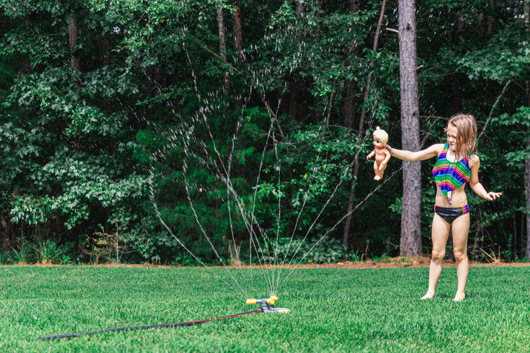 Girl playing in the yard with a doll and lawn sprinkler