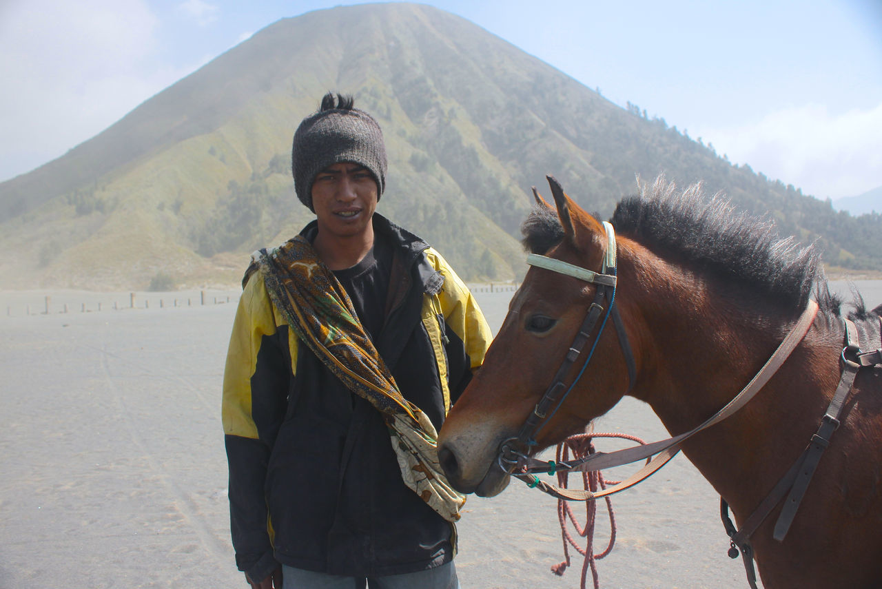 Portrait Of Young Man By Horse On Field With Mt Bromo In Background