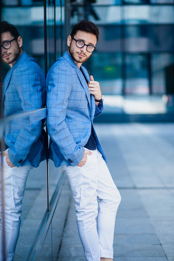 Young Businessman in Urban area Adult Architecture Beautiful People Clothing Day Focus On Foreground Glass - Material Males  Men Outdoors People Real People Reflection Standing Two People Well-dressed Young Adult Young Men