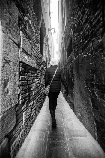Adult Architecture Black&white Blackandwhite Brick Wall Bricks Building Exterior Built Structure City Cold Day Full Length Leading Lines Light And Shadow Monochrome One Person One Woman Only Only Women Outdoors People Real People Rear View Stone Material The Way Forward Walking