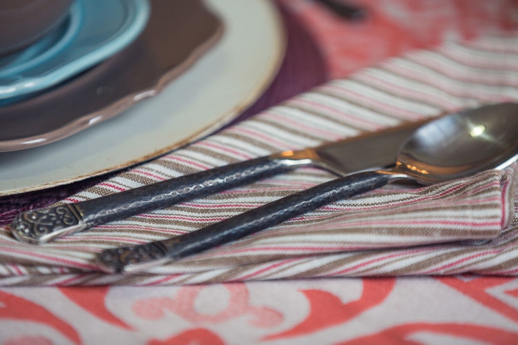 Close-up of silverware on napkin at dining table