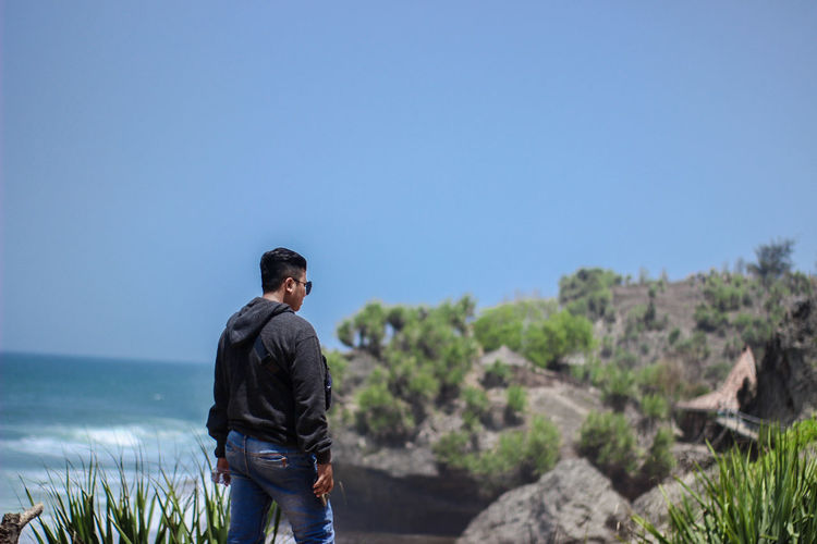 Rear view of man standing against sea