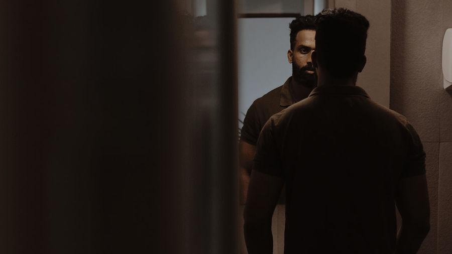 Rear view of man looking through window mirror