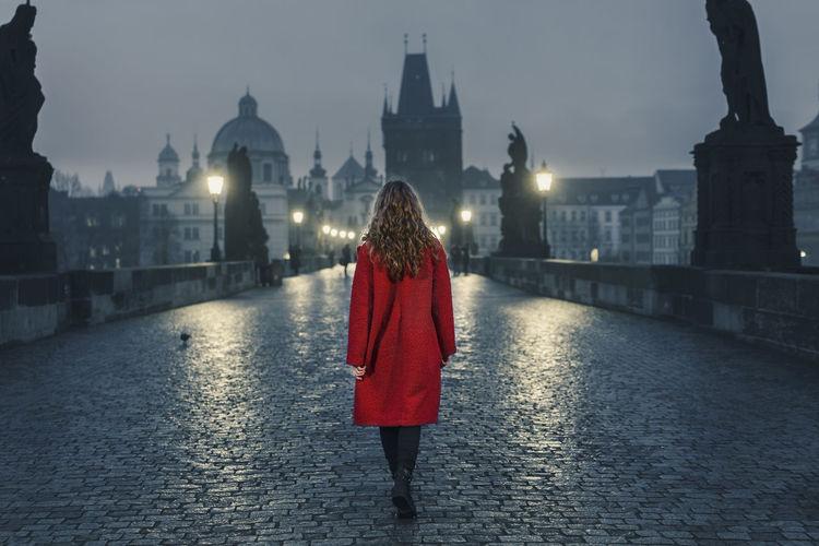 Rear view of woman standing on bridge against buildings in city