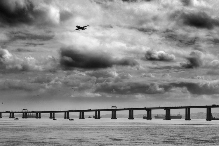 Silhouette Rio-Niteroi Bridge Over River Against Airplane Flying In Cloudy Sky
