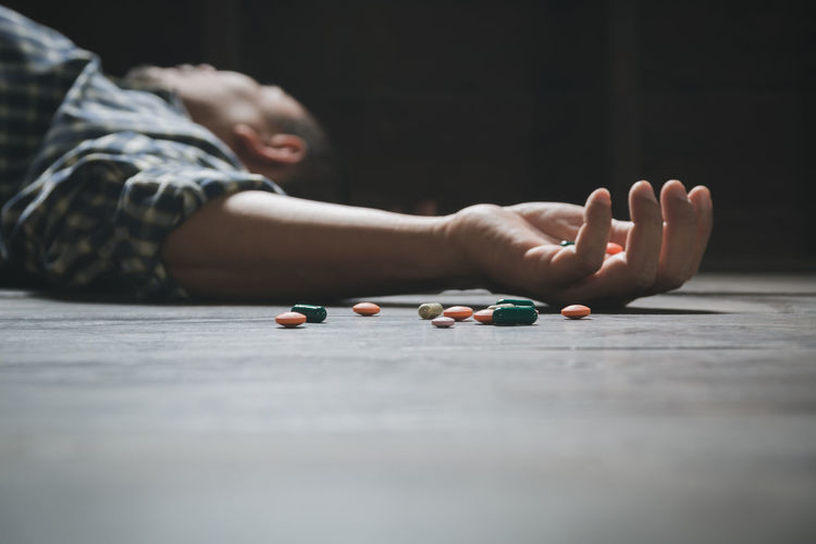 Man lying by pills on floor at home
