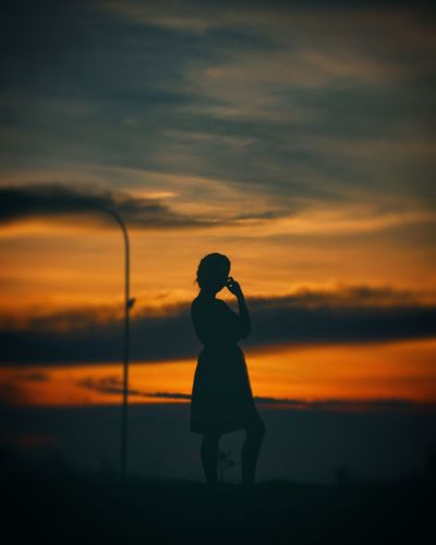 Silhouette woman standing against orange sky during sunset