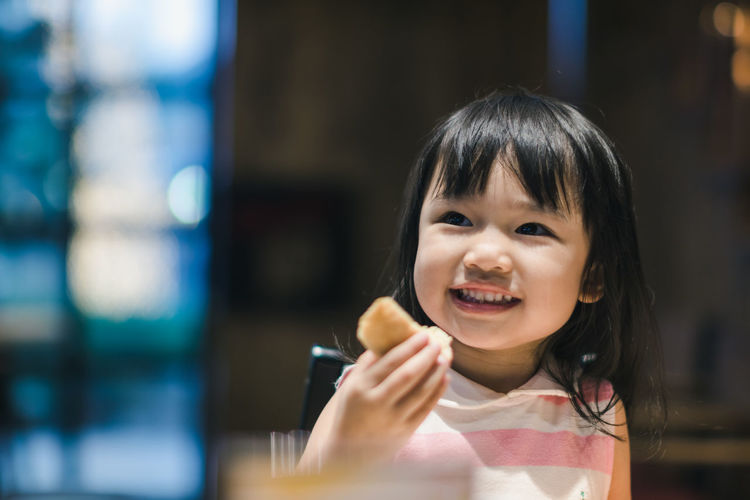 Cheerful girl holding food while looking away
