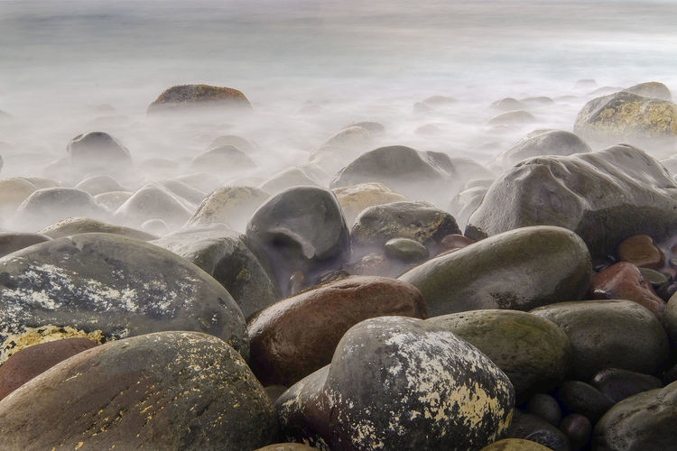 Pebbles at beach against sky