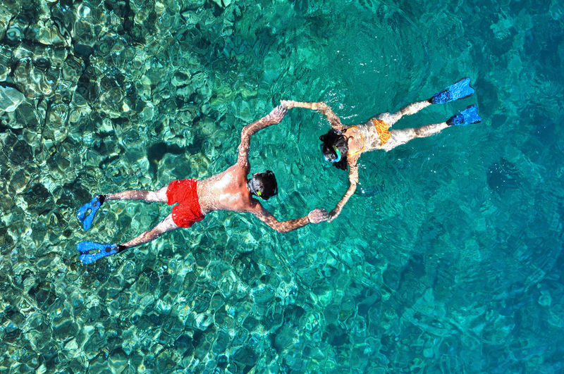 Above view of a snorkeling couple Above Activity Adventure Couple Hand In Hand Leisure Activity Love Man And Woman Marine Ocean Outdoors Recreation  Relaxation Ripple Sea Shallow Snorkel Snorkeling Sunny Swimming The Color Of Sport Underwater Water Water Reflections Wave