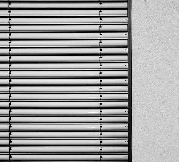 Urban Perspectives Minimalism Street Photography Black & White Monochrome Pattern Wall - Building Feature Built Structure Architecture Window Blinds Safety Security Building Exterior No People Protection Closed Wall Day Close-up Backgrounds Shutter Metal Full Frame Iron Silver Colored Architectural Detail The Minimalist - 2019 EyeEm Awards