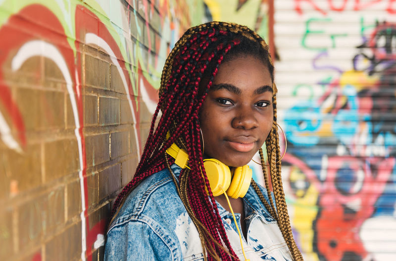 Portrait of smiling young woman against wall