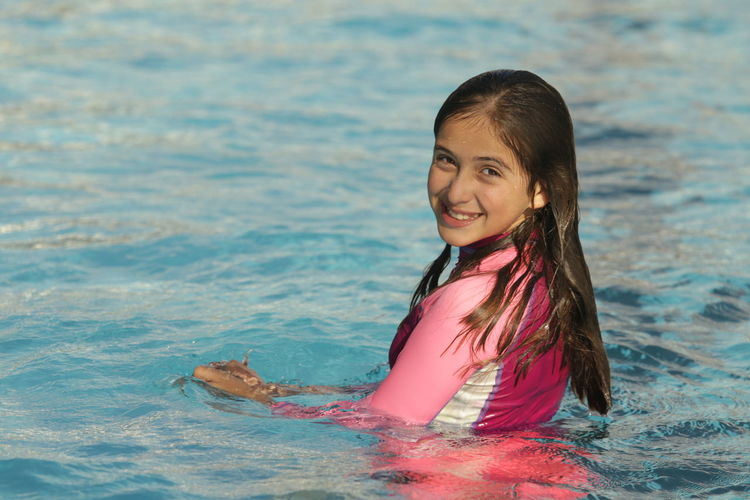 Portrait of happy girl in swimming pool