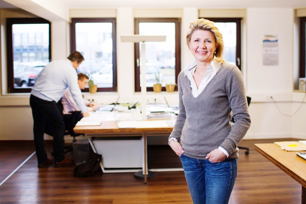 looking at camera, smiling, desk, indoors, portrait, office, happiness, table, standing, focus on foreground, casual clothing, mature women, mature adult, occupation, day, real people, business, cheerful, women, teamwork, young adult, people
