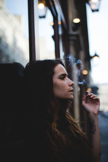 Young woman smoking while leaning on window