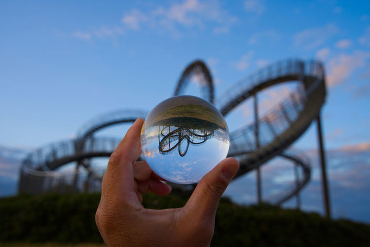 Close-up of hand holding crystal ball against roller coaster