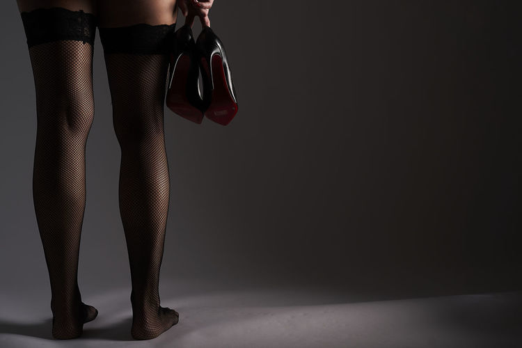 Low section of woman wearing stockings and holding high heels against gray background