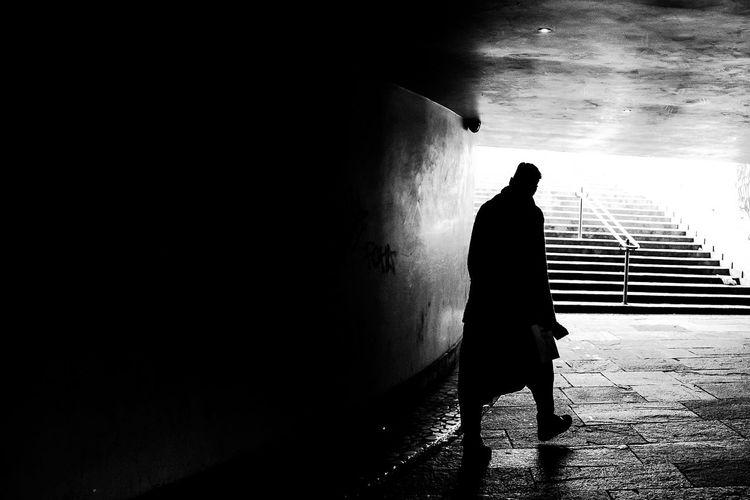 Rear view of man walking at the end of subway