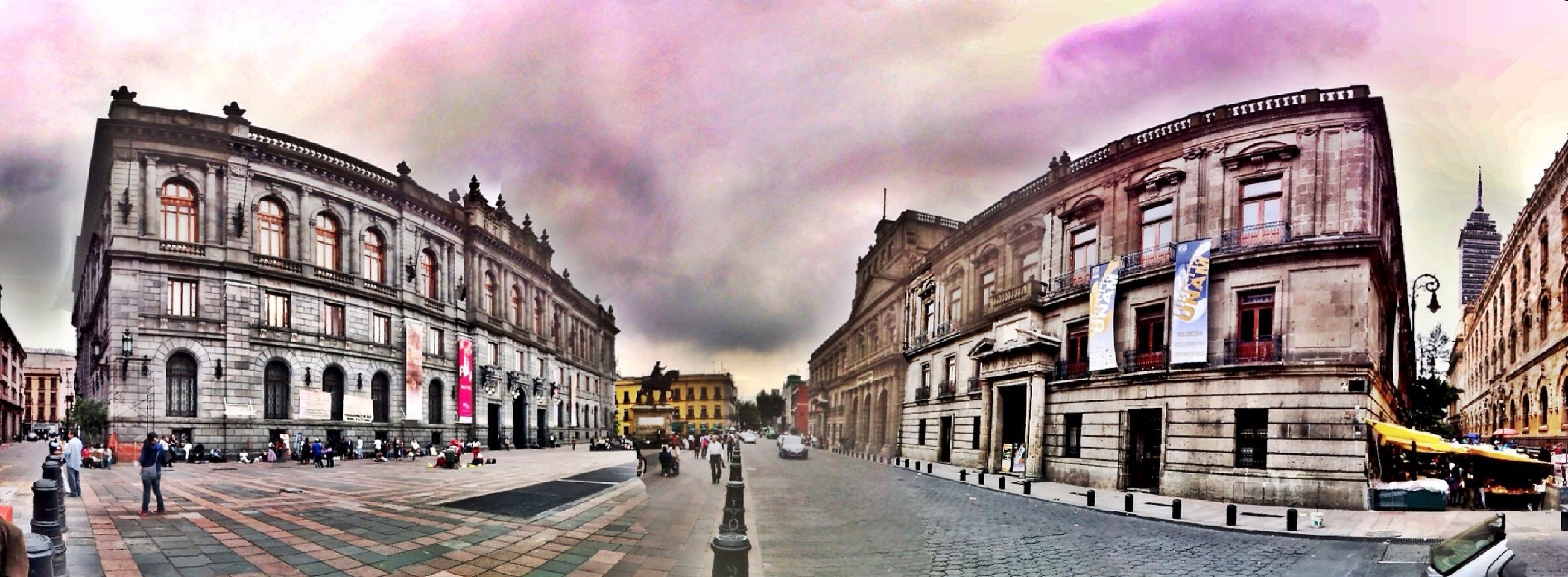 building exterior, architecture, built structure, sky, street, the way forward, cloud - sky, diminishing perspective, cloudy, city, building, road, weather, incidental people, transportation, overcast, vanishing point, car, residential structure, cloud