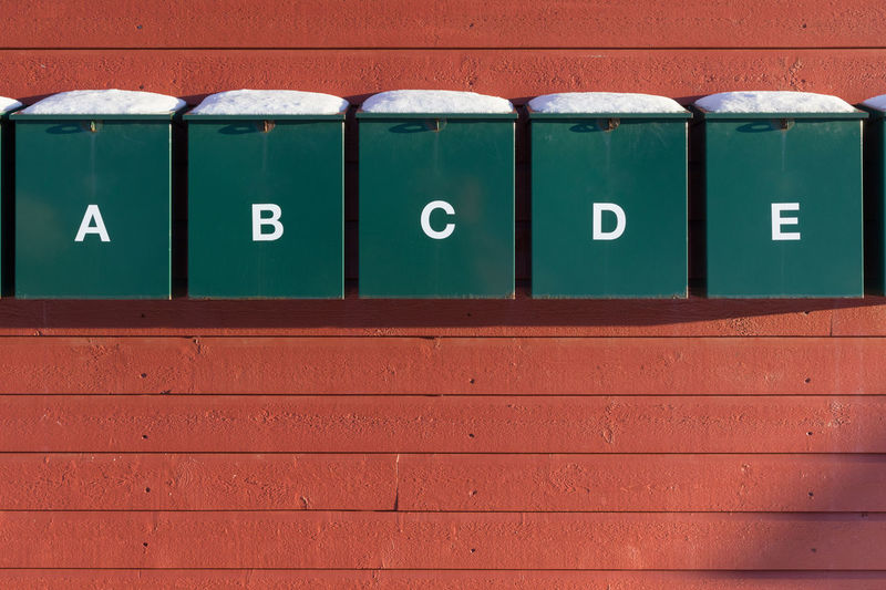 Snowcapped green colored letter boxes with capital letters A, B, C, D and E on a red colored wooden house wall Red Snow Outdoors Letter B Letter A Letter C Letter D Letter E Green Color Wood - Material Wood Paneling Sunny Winter Cold Temperature Close-up Full Frame Number Communication No People Sign Wall - Building Feature Side By Side In A Row Architecture Indoors  Information Built Structure Text Information Sign Wall Day Guidance Letter