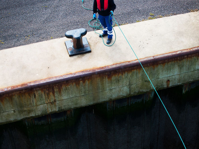 Low section of man holding rope standing by bollard