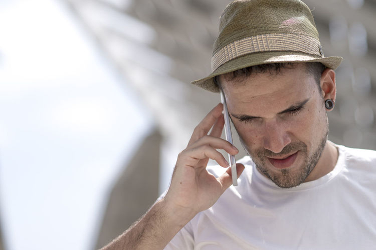 Man wearing hat while answering smart phone