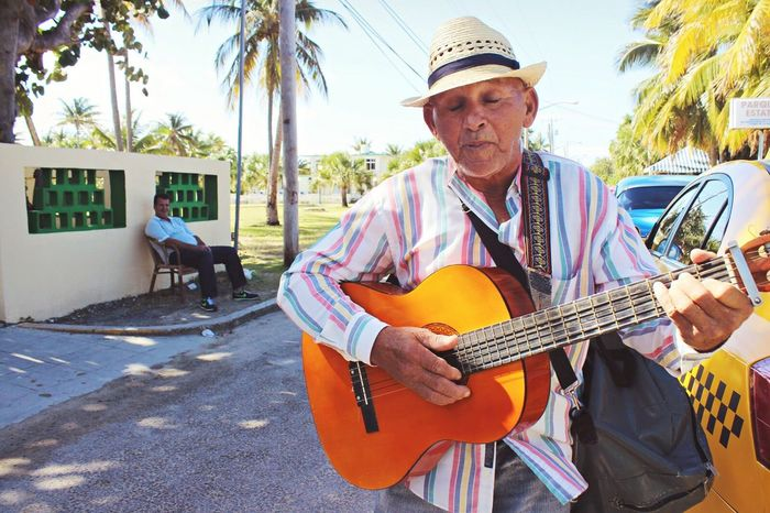 Senior Adult Music Guitar Senior Men Hat One Person Musical Instrument Casual Clothing Happiness Plucking An Instrument Adults Only Playing Only Men One Senior Man Only Tree People Lifestyles String Instrument Leisure Activity Men Uniqueness