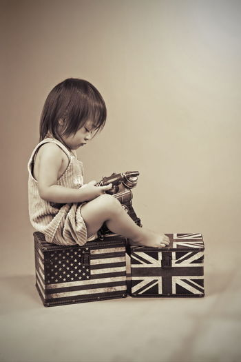 Side View Of Girl With Rotary Phone Sitting On Boxes With National Flags Over Beige Background