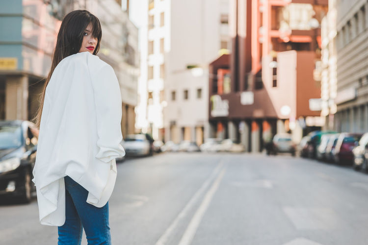 Beautifu young woman with white jacket cross a street Crossing The Street Building Exterior City City Life Day Hairstyle Lifestyles One Person Real People Street Walking Women Young Adult