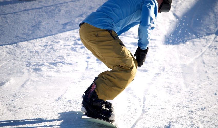 Low Section Of Man Snowboarding On Field