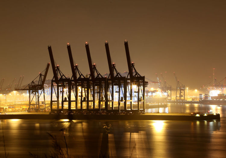 Cranes at commercial dock against clear sky at night