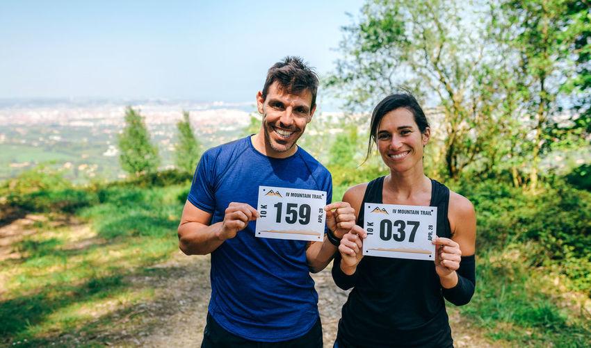 Portrait of smiling athletes holding label on mountain