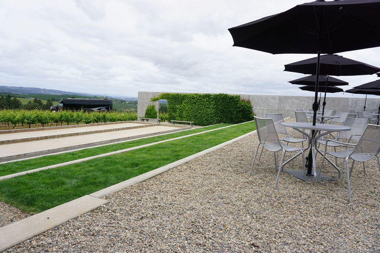 Chairs and tables under parasols by field against cloudy sky