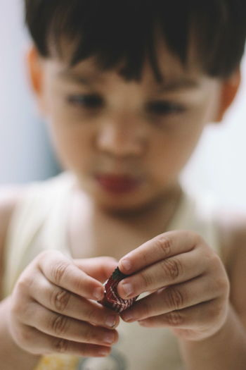 Close-Up Of Boy Holding Chocolate Indoors
