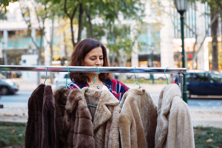 Mature Woman Looking At Fur Coats In City At Market