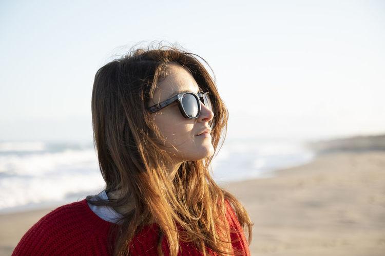 Portrait of woman on beach against sky