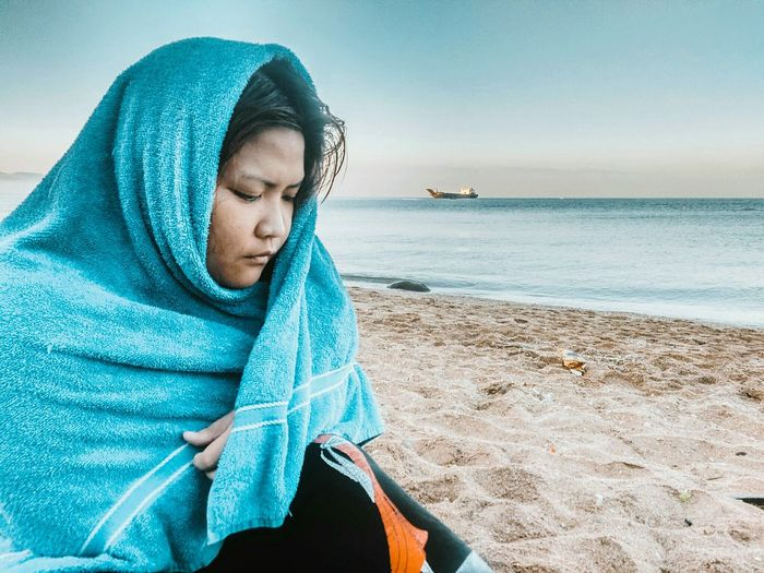 Woman wrapped in towel while sitting at beach