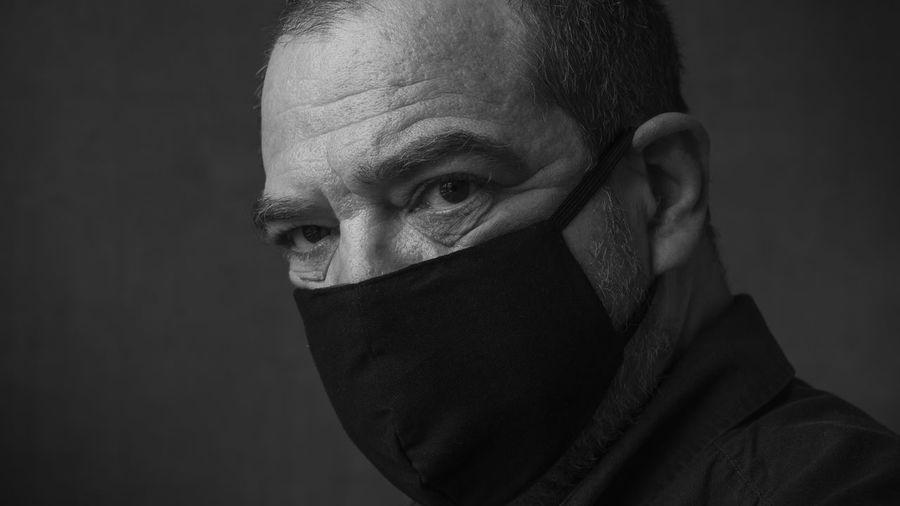 Mature man in black medical mask close-up face