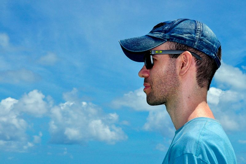 Side view of man against blue sky
