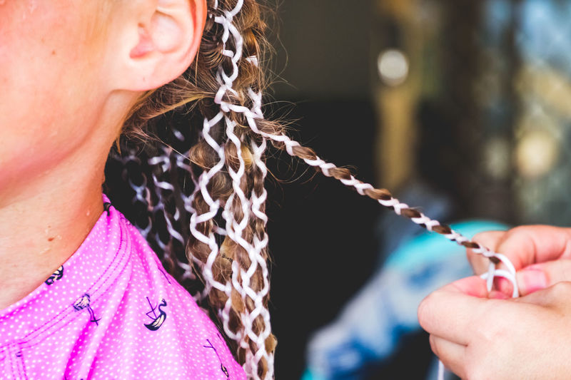 close up of a young girl getting thread braids in her hair Real People Women Lifestyles One Person Focus On Foreground Chain Day Leisure Activity Human Body Part Human Hand Adult Close-up Holding Sunlight Hand Females Girls Outdoors Midsection Hairstyle Braids Thread Long Hair