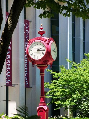 Red clock at Indiana University. Architecture Bloomington, Indiana Built Structure Circle Clock Day Green Color Indiana Indiana University Information Sign Low Angle View No People Ornate Outdoors Red Red School Telephone Booth Time Trees The Color Of School