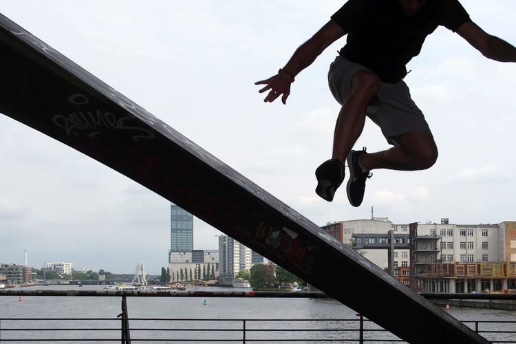 Man jumping on bridge over river in city against sky