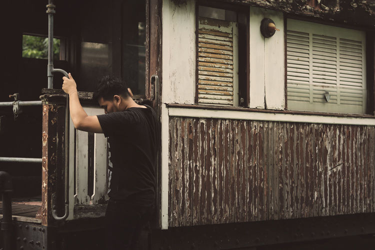 Man standing by window of building