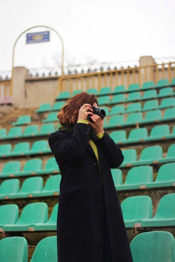 Woman photographing while standing at stadium