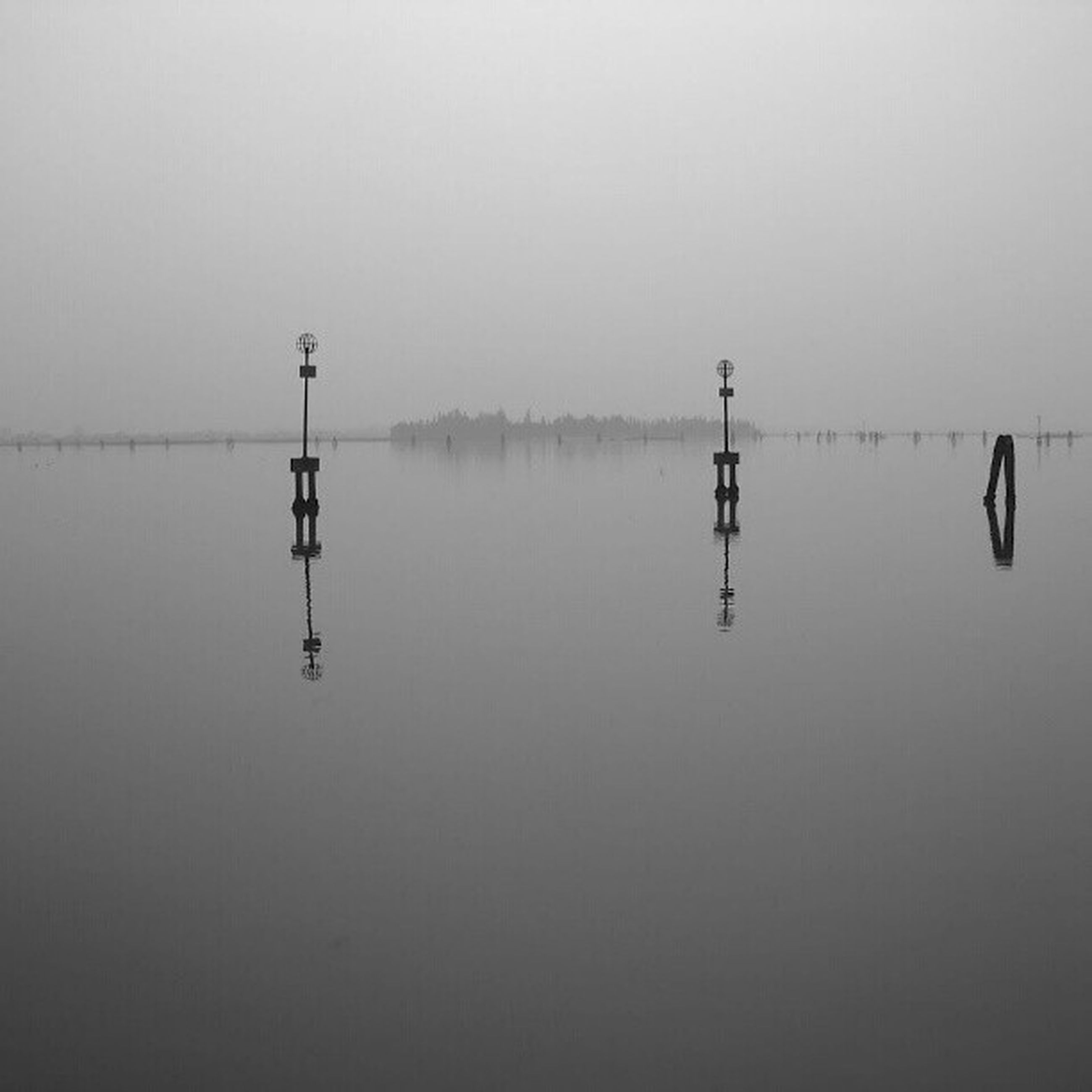 water, copy space, tranquility, reflection, clear sky, tranquil scene, lake, waterfront, scenics, nature, beauty in nature, sea, foggy, no people, calm, sky, outdoors, day, idyllic