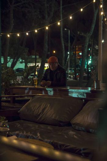 Man sitting on illuminated street lights at night