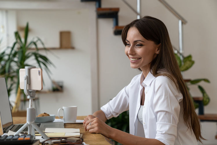 Portrait of smiling young woman on table