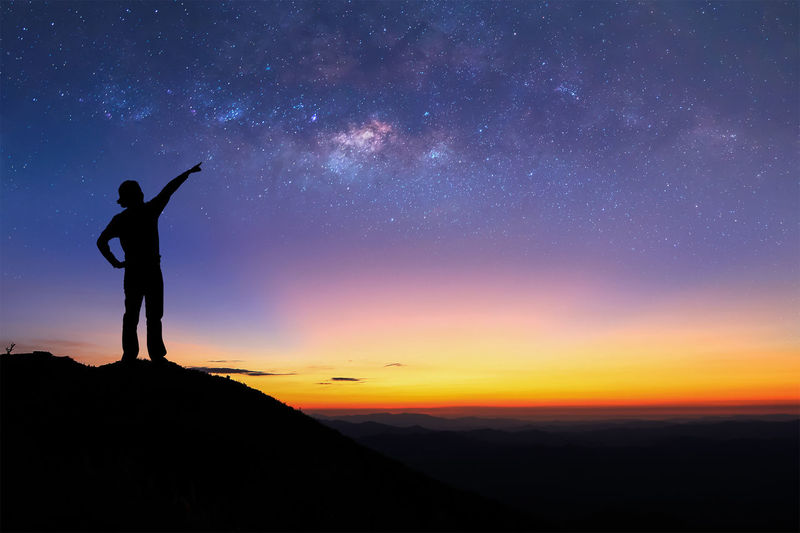 Silhouette person standing on mountain peak while pointing at stars in sky at night