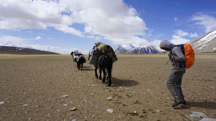Men standing on mountain road against sky