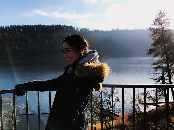 Smiling young woman standing at observation point by lake during winter